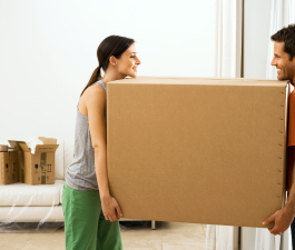 Couple moving house, carrying large cardboard box in sparse room, face to face
